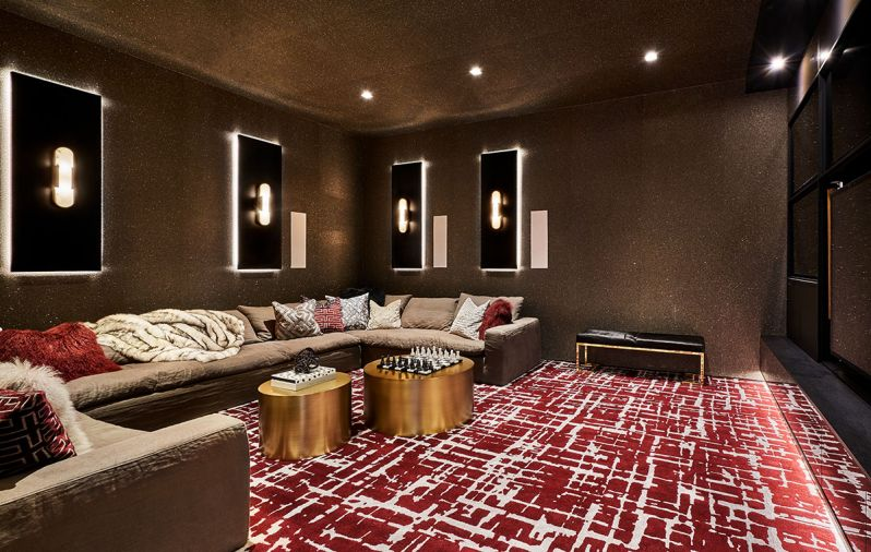 A Cloud sectional in performance linen by Restoration Hardware Modern adds comfort to the theater experience. Luxurious gray and oxblood jewel tone custom wall-to-wall Davis & Davis carpet adds plushness underfoot. Thayer Coggin Design Classic golden drum tables add sparkle.