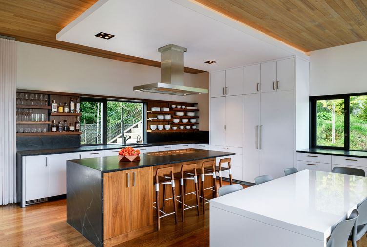 This kitchen was built for entertaining, with an open layout and plenty of space for cooking, hosting, and socializing. Dark soapstone counters contrast with white laminate cabinets and walnut accents, with oak flooring and a stained Western red cedar ceiling to match the exterior of the home. The oven, microwave, refrigerator, and dishwasher are from Miele, while the cooktop is from Monogram. A Blanco sink is finished with a KWC Luna faucet.