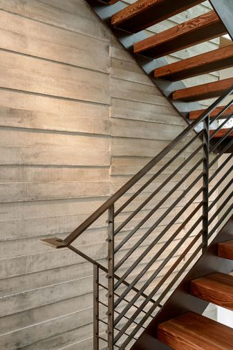 A board form concrete wall adds texture and visual interest to the stairwell.