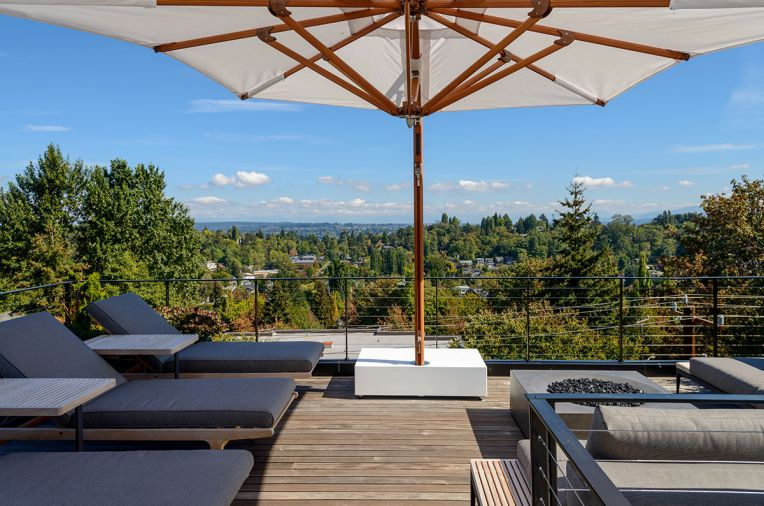 The rooftop patio features a built-in firepit and views of the Cascades and Puget Sound.
