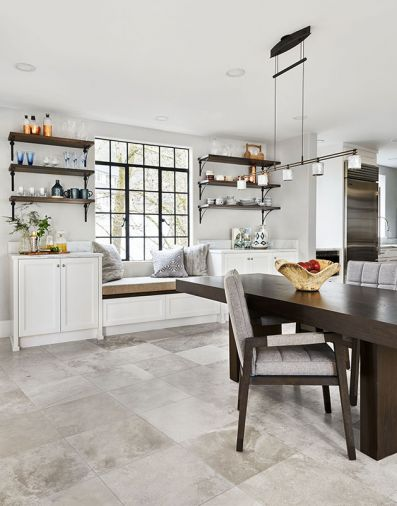 The family's dining area got cozier with the addition of a window seat centered beneath a steel window and flanked by a pair of built-in white cabinets crowned with a pair of triple-bracketed shelves in a space once occupied by an oversized refrigerator. Adjustable Holtkötter lighting over table.