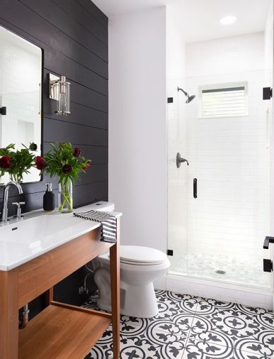 The guest bath features an eye catching black-and-white, large-format porcelain tile from Statements Tile along with a more casual, black-painted shiplap wall and freestanding shower.