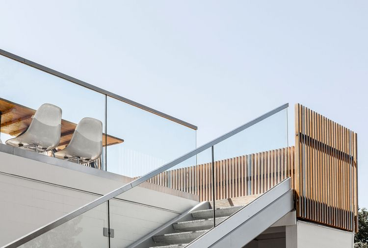 Steel stringer stairs with a cantilevered glass guardrail and precast concrete treads provide access to the deck while preserving the view.