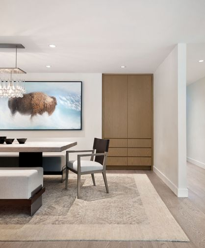 In the dining room, focal point artwork by Aaron Hexom depicting a buffalo—an animal that has special significance to the family—adds an ethereal quality, and a crystal droplet light from Bone Simple is a decorative touch. Rug from Stacey Logan.