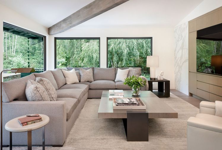 Adding to the neutral-but-comfortable vibe, the formal living room's sectional and lounge chair are from A. Rudin, with fabric by Holly Hunt, coffee table by LUMA, side tables from Restoration Hardware and Elan Atelier, and rug from Stacey Logan.