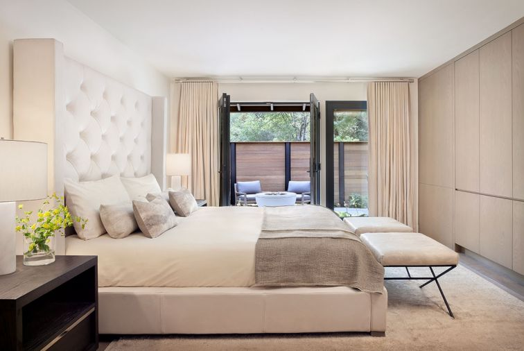 The master bedroom is a serene retreat overlooking a private patio, with a bed and nightstands from Restoration Hardware, Schumacher benches covered in Townsend Leather, and light-colored accessories from Room & Board, Village Interiors, Rubelli, C&C Milano, rug from Stacey Logan.