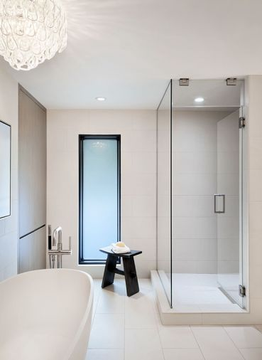A crystal chandelier-style fixture from Vistosi adds some glamour to the pristine master bath, which is complete with a freestanding tub from Signature Hardware, a steam shower, and white porcelain tiles from Florida Tile.
