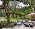 The family's lush outdoor retreat, including access to Issaquah Creek, a lawn and meadow, and a putting green, was created by landscape architects Land Morphology. On the patio, outdoor furniture from Restoration Hardware is shaded by a Barlow Tyrie umbrella, and hanging chairs from CB2 and poufs from Article are whimsical options.