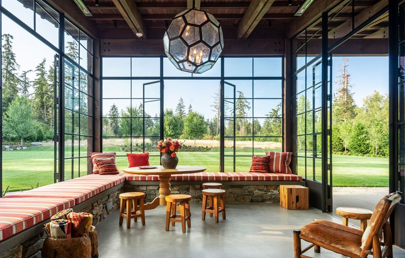 The sunroom is marked by a large, hexagonal-shaped hanging pendant custom designed by Kerry Joyce that is an unexpected contrast to the other, more rustic elements in the space. Steel-framed casement doors can open to let in fresh air, and an inglenook, or partially enclosed fireplace creates a sense of coziness. The sunroom's meadow views are enhanced by pops of color in cushions with fabric from Romo and Great Outdoors, and fabricated by Washington company Island Custom Upholstery. Pendleton throw blankets and a classic table and stools by Tirto Furniture are a natural fit for the outdoorsy space, along with folding chairs from locally based Terris Draheim.