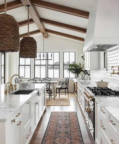 A modern palette of white, black, and gray pervades this farmhouse-style renovation, enhanced by brushed brass accents and fixtures in both the carriage and main house kitchens, which include cabinet design by Signature Design & Cabinetry. The water view is paramount from the kitchen and dining room, where a mix of the client's own furniture and vintage pieces tie in with the marble countertops and wood accents. Windows by Sierra Pacific.