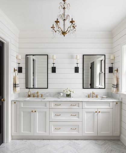 The master bathroom and powder room tie in multiple elements from the home, including marble countertops, black-framed mirrors and glass shower door that imitate the windows found elsewhere, shiplap walls, and brushed-brass hardware and fixtures. A cloudlike gray and white wallpaper in the powder room backs the client's own vintage pine dresser repurposed into a vanity, with wall-mounted faucet and an antique mirror to round out the look.