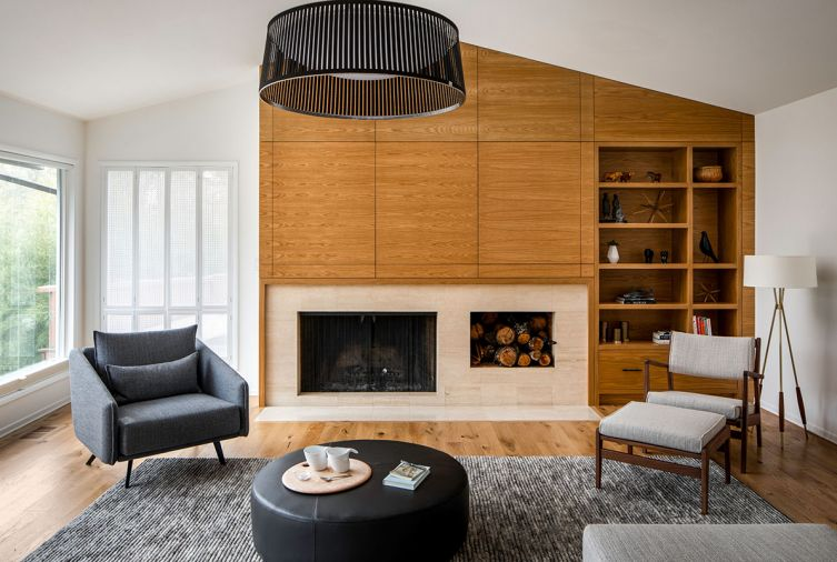 "The living room is anchored by a new wood-wrapped fireplace wall with built-in shelving to display the family's collected items. To ""ground the bright, voluminous space and lower the seating area to a cozier human scale,"" explains designer Allison Larsen, she added a black Solis Drum pendant light from Pablo that mirrors the round ottoman below."