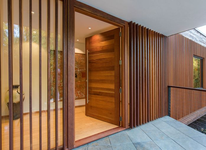 Handcrafted mahogany entry door flanked by mahogany spaced-board screen over a fixed glass pane.