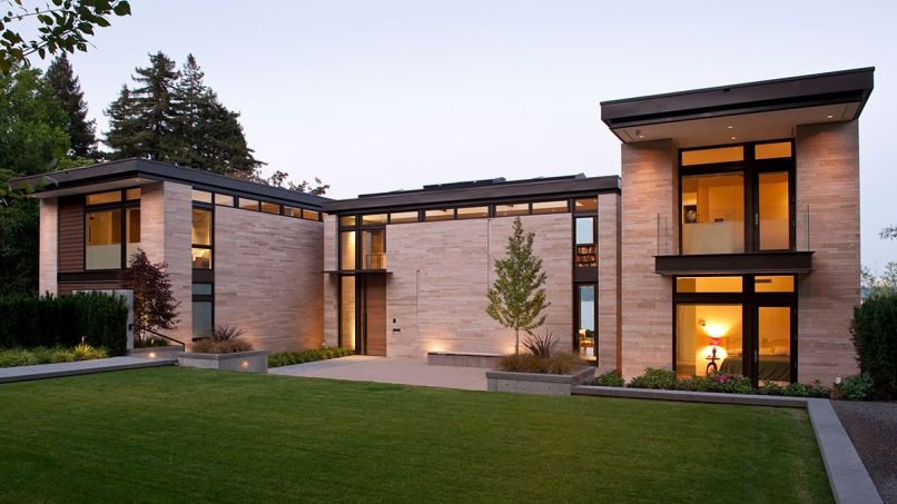 Amber Rose flame stone clad exterior is cut and stacked into three varied sizes to show texture and complex color range. Clerestory windows wrap the home for light yet ensure privacy from street. The Scot Eckley, Inc. landscape design features a gingko tree in a crushed gravel court at right; red Japanese maple left. Photo © Rob Perry