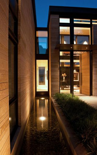 Two water features, running perpendicular to house, appear as if they carry water coursing through the house. Horizontal oak plank entry door echoes stacked stone façade. Large porcelain tile entry flooring is by Porcelanosa. Wndows are clad exterior/wood interior. Photo © Rob Perry