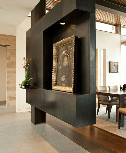 A very sculptural cold rolled blackened steel structure – a creative zone at the entry - purposefully interrupts a view through the dining room, while providing display areas for the homeowners' treasured painting by Colorado artist Ingrid Magidson, and an equally sculptural plant. Photo © Rob Perry