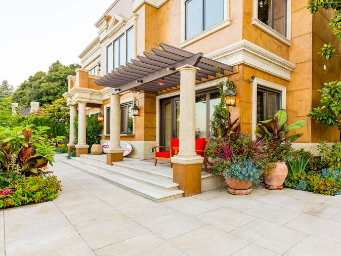 The French limestone terrace acts as a wonderful foil for the joyful color display. Accenting the limestone and architecture, fine Italian Impruneta terra cotta containers are placed throughout the landscape.