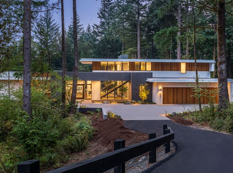 Sited on a 1.2 acre, heavily forested property, this home in the Portland area feels enveloped by the landscape. The exterior blends traditional stucco in two different shades as well as vertical red cedar. Wide overhangs protect the siding while also creating strong horizontal lines in contrast to the vertical cedar. A reflecting pool near the front entrance pulls in light and sets a spa-like tone even before you step inside.