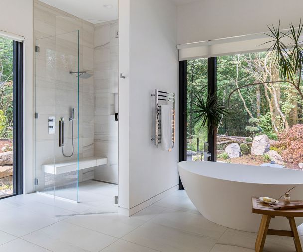 Mosa porcelain tile lines the bathroom floors. Pictured here is the ground-floor master bath, with massive walls of glass framing forest views. The master bath includes a Badeloft freestanding tub and Aquabrass fixtures.