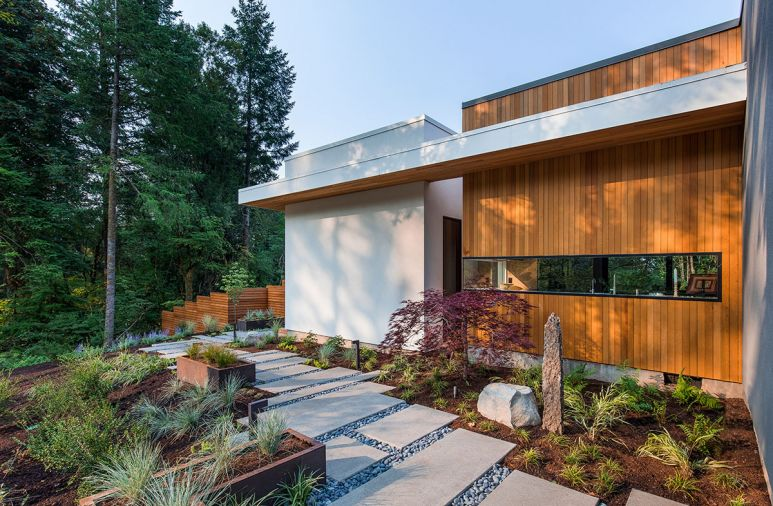 The outdoor walkway that connects the patio to the master bedroom. The exterior is clad in traditional stucco and tongue-and-groove vertical cedar siding.