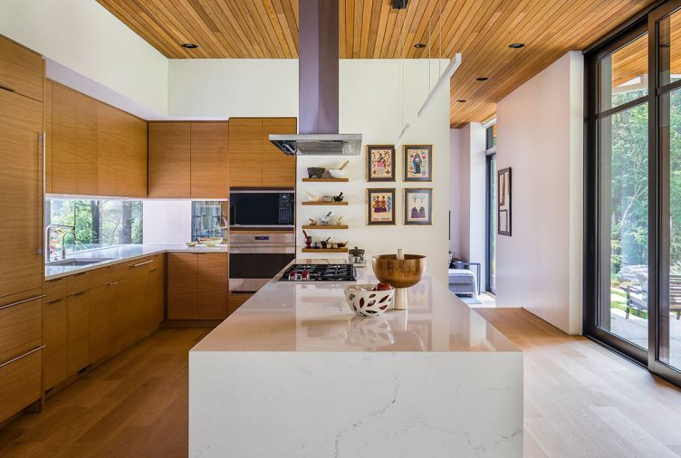 "The kitchen ceiling using the same red cedar used for the exterior soffits creates a sense of continuity between indoors and outdoors. ""We didn't want to just have a lot of white surfaces, but we also didn't want all wood surfaces, so this was a blend of bringing that warmth into the house without having it take over,"" says Tim. The kitchen cabinetry and floors are white oak, while the wrap-around cabinetry in the entryway is walnut. The sleek kitchen is fitted with a Miele dishwasher, Miele oven, Wolf Cooktop, and a Sub-Zero refrigerator."
