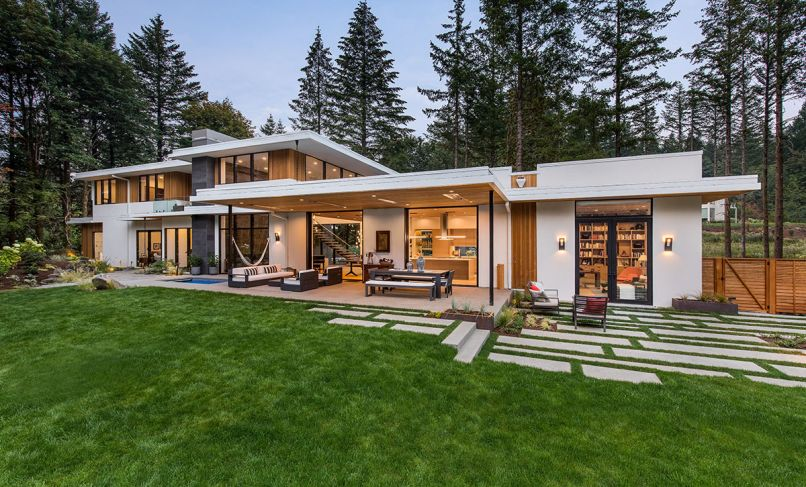The clients, who work nearby, requested a modern home with simple, clean lines to fit within the heavily forested 1.2-acre site and to embrace outdoor living throughout the year. They requested the home to be truly livable in the cool northwest climate with natural daylight and filtered views of the forest. Indoor/outdoor living is emphasized throughout the design. A protected acid-washed concrete terrace is furnished with Restoration Hardware seating, a Marbella Metal Rectangular table.