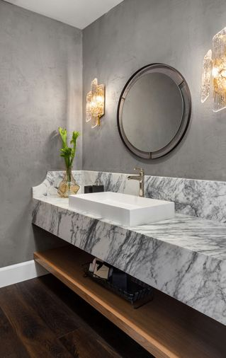 A circular mirror, Mont Blanc marble counter, Piedmont wall sconces by Corbett, and a white oak shelf combine to evoking the aura of a European boutique hotel on the main level powder room.