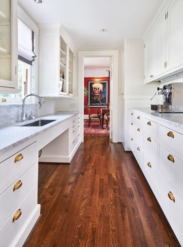 Original butler's pantry glass cabinetry and cup bin pulls left. Jeff's hidden VRV HVAC panel design is held up with earth magnets. Currant red dining room walls and oversized poster art seen beyond.