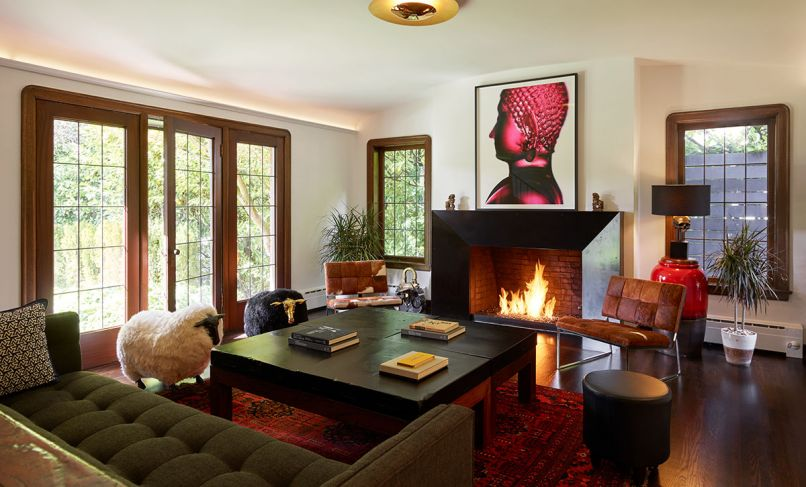 Key architectural elements of this 1927 Tudor style home with French Normandy flourishes remain intact today: voluptuously curved mahogany windows, trim and leaded glass windows restored to their former glory. In the living room, Chadbourne + Doss Architects brought the existing fireplace front and center with a faceted blackened steel surround. Gleaming Blaze lighting by Modern Forms draws the eye to new cove uplighting. Homeowners' artwork, a Buddha photograph, adds drama to historic architecture.