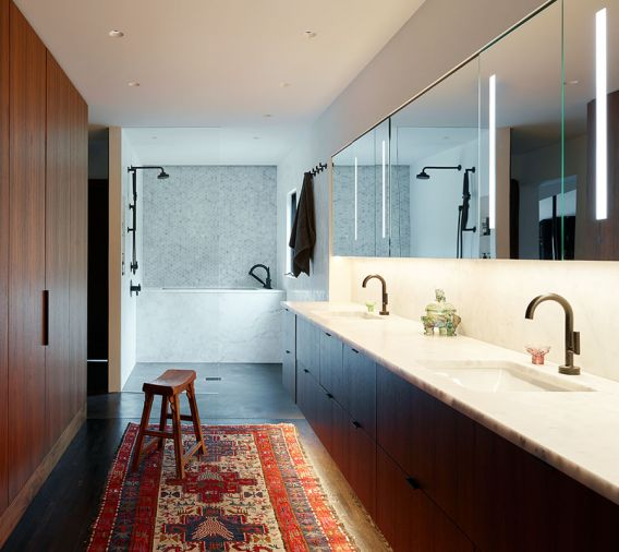 Gone are the maze of separate small masterbath rooms, now the suite is unified by a sleek double-sink walnut vanity, Milestone plaster flooring, walk-in shower, Brizo Odin fixtures, and a custom marble soaking tub.