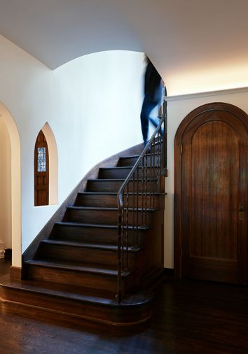 Restored original architectural elements include arched entry closet, curved staircase and niche.