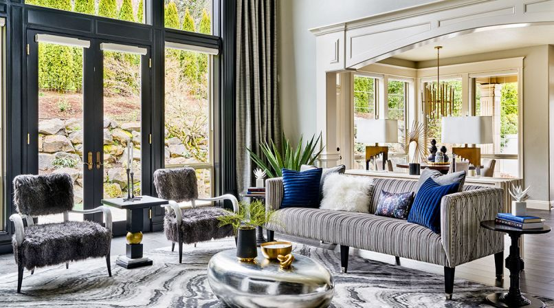 To open up the living areas, heavy traditional elements were eliminated, including quadruple crown moldings, massive Roman columns that blocked passageway from the living area to dining nook. Edgy fur chairs with bone pair with pinstriped velvet sofa.