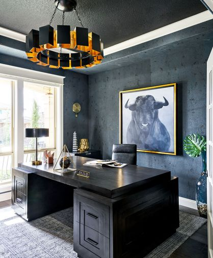 The husband's office walls heavily textured masculine-feel by Bravura Finishes. Arteriors chandelier echoes brass glow. Bullish thematic artwork by Leftbank; desk by Noir.