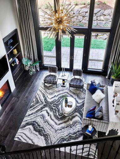 The view from the central staircase highlights the updated fireplace with floor-to-ceiling chimney and dark wood built-ins. Sherwin Williams Caviar painted window trim and molding adds drama. Hudson Valley chandelier provides glam. Feizy rug underscores modern design. Bernhardt sofa with Art Deco velvet upholstery and furry chairs give comfort.