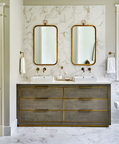 Charlie Zagaroli's Cela Shagreen Fog Double Vanity from Restoration Hardware features burnished brass trim. A pair of Renwil mirrors continue the brass theme set here against the Z Collection Calacatta Oro tile as backsplash. Brass wall mounted Delta Trinsic faucets and Lacava Cube Lav sinks complete the look.