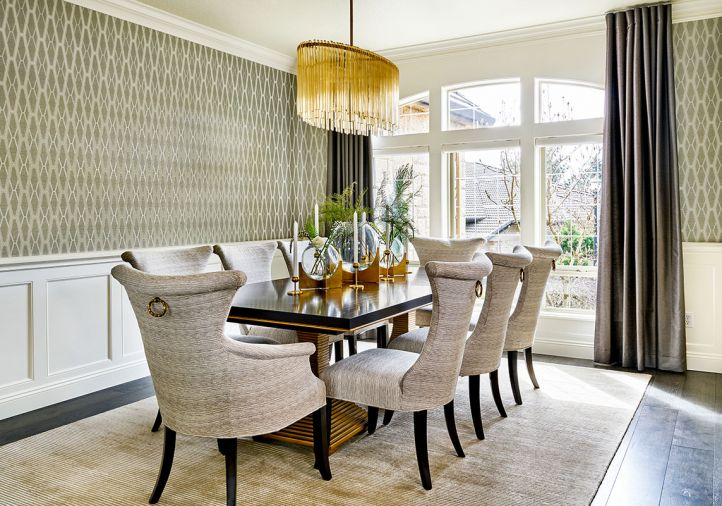 Although no structural changes were made to the dining room, the interior design decisions altered it dramatically: Wallquest Modern Elegance wallpaper that crowns the original classic wainscoting; replacing a traditional wedding cake chandelier with an elegant oval Arteriors chandelier to become the icing on this cake.