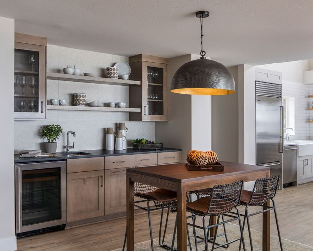 To create continuity, the main floor features a sandy-colored, weathered-wood-like flooring that extends throughout the space, including into a breakfast bar and beverage area adjacent to the kitchen. Here, dark gray granite countertops are flecked with shimmer, and the shape and finish of the light fixture relates to the gold trim on the bar island. Cabinetry is maple with a pumice finish, which nods the stone tile material that clads the home's fireplace.