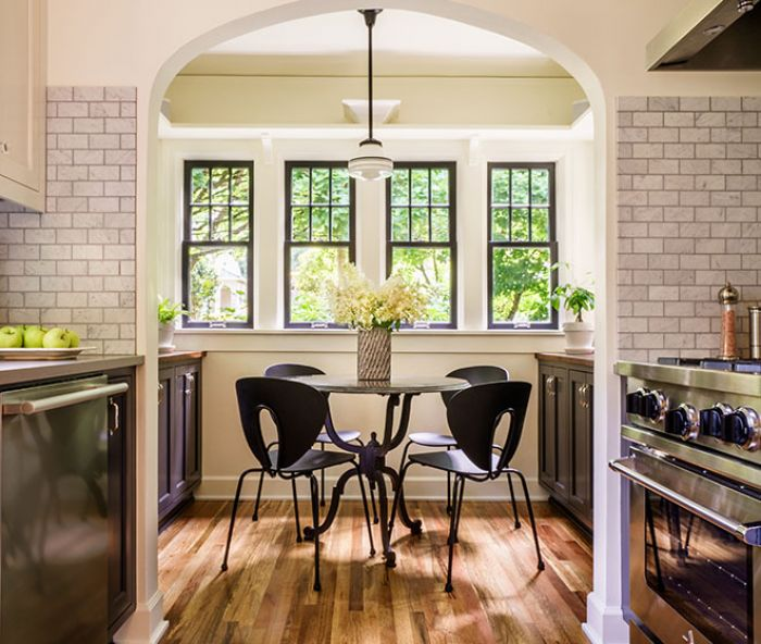 There were two elements of the 1925 cottage kitchen that Chelly knew she would maintain: the arched entry into the breakfast nook and the original windows and glass. Adding display shelves with corbel brackets increased storage space, as did the construction of new cabinetry painted Benjamin Moore Wrought Iron like the kitchen cabinets. Mixing modern with period correct furnishings inspired the combo of comfy Design Within Reach Globus chairs paired with a traditional wrought iron legged table from Rejuvenation.