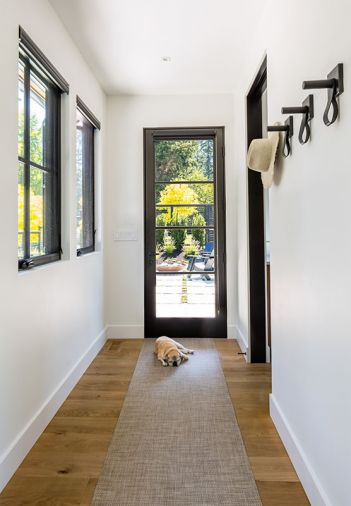 Metal clad Loewen windows have wooden interiors, painted black. Portella door opens to back patio, Paloform Bol adds pop of color and contrast. Golden locust tree adds halo of gold to Treherne's landscape design