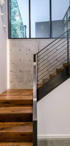 Walnut-stained oak staircase with steel railings travels from garage to Quantum entry door and black-stained sapele mahogany windows with aluminum cladding.