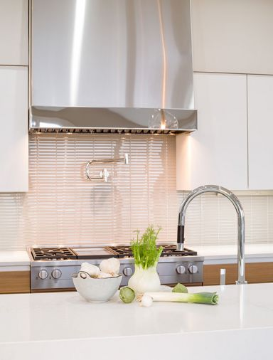Eye-catching range 1x6 backsplash by Dal Tile Color Wave in Feather White.