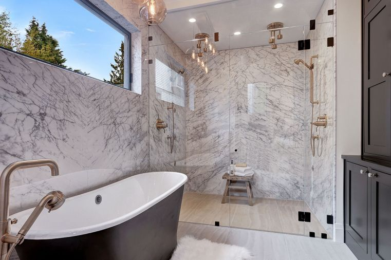 Master suite shower features dual Brizo luxe gold rain showerheads from the Litze collection. White Carrera honed marble walls extend throughout. Black matte exterior cast iron Kateryn Signature Hardware bathtub ties to shaker style cabinets at right.