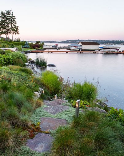 The pathway down to the pebble beach is trimmed with wooly thyme. Hardstem bulrushes protect against wave erosion and stabilize soil. Custom pathway lights by Broadhurst + Associates.