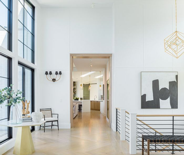Dumont reiterates black, white, and gold palette throughout entry: painted wood paneling, steel staircase, Visual Comfort Cubist pendant, Arteriors sconces, hex-shaped table, and artwork. French doors flank Marvin aluminum clad windows.