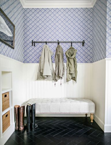 In the mudroom, gloves and hats can be stashed in woven storage bins, boots can be removed while sitting on an upholstered bench, and coats can be hung on a series of convenient hooks.