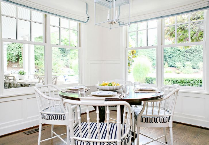 Informal family meals can be enjoyed at the table in the kitchen. White walls, chairs and light fixture help bring airiness to the room's corner while the wood table keep it grounded. Outside are a patio dining area and vegetable garden also created by Trove.