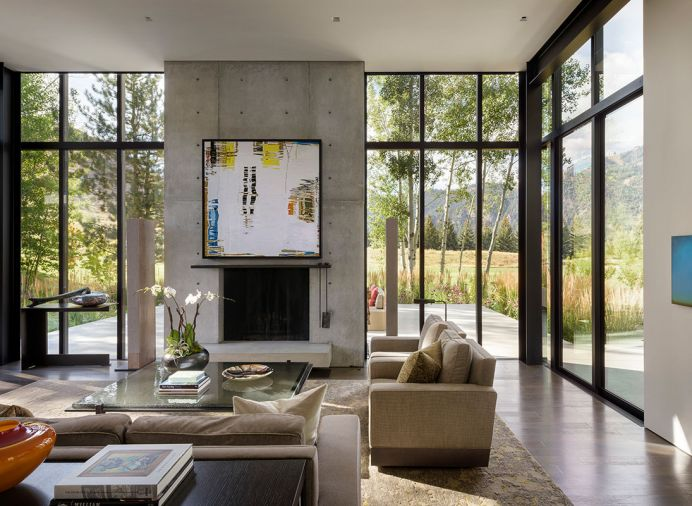 Barbara Vaughn photo of water on art lift reveals oversized TV on concrete fireplace with hot-rolled steel - wax finish mantel. Custom Gary Leeds audio speakers; William Morris glass art on custom Lucas Interior table. Lucas custom sofas; Driscoll Robbins rug.