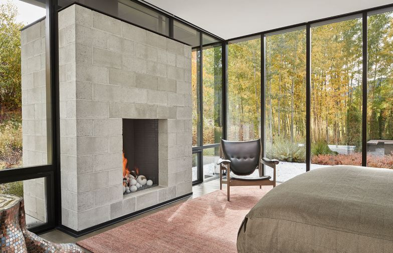 Finn Juhl Chieftain chair reproduction and artful kaleidoscopic mosaic tree trunk adjoin master hot-rolled steel fireplace. Lucas tweed coral/burgundy rug from Driscoll Robbins.