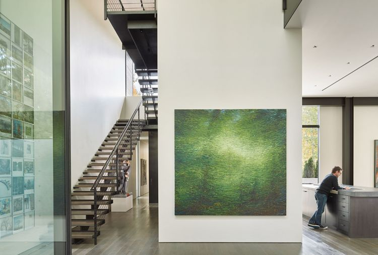 "Lawrence Fodor (Friesen Gallery) oil on canvas entitled ""Rain Forest"" graces the entrance on a double-height foyer wall. The kitchen island is seen at right, while a sculpture features two businessmen fighting over money at left beneath the staircase rising to the second floor."