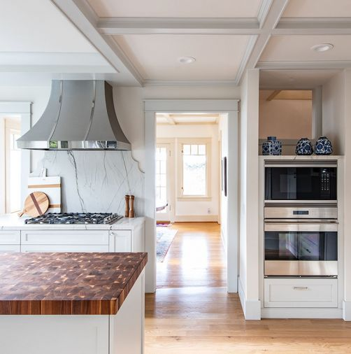 The homeowners requested that appliance spaces were maintained. A pass through to the left of the cooktop gives a glimpse of the rest of the home, while a cutout above the wall ovens provides light to a hallway.